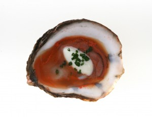 This oyster was fed a mixture of carrot juice, green cardamom, and aquarium salt that had been blended with a high-speed rotor-stator homogenizer to reduce the liquid's particle size below 10 microns. Larger particles could clog the oyster's gills.  The oyster ate the mixture and flavored itself while it was still alive.  It was served with crème fraîche and chives.